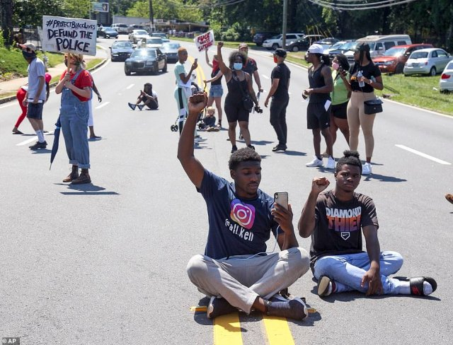 Several protesters blocked traffic and sat in the middle of the road during the demonstration against police brutality on Saturday