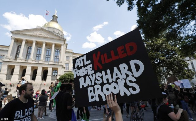 Protesters march near the Georgia Capitol on Saturday after an overnight Atlanta Police Department officer-involved shooting which left a black man dead at a Wendy's restaurant