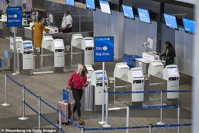 Ein Reisender mit einer Schutzmaske verlässt den Check-in-Schalter von United Airlines Holdings Inc. am internationalen Flughafen von San Francisco