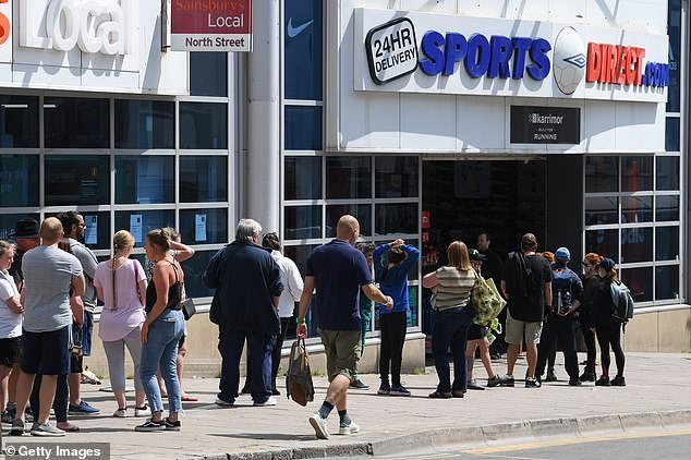 BRIGHTON: Shoppers queue outside a Sports Direct store on Monday as non-essential shops open for the first time in three months