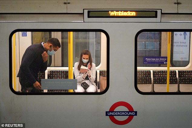Sadiq Khan told LBC: 'This is part of the new normal. The reality is that for the foreseeable future - I predict for the next year or so - wearing face coverings is going to become the norm rather than the exception.' Pictured: Passengers wearing masks on the Tube