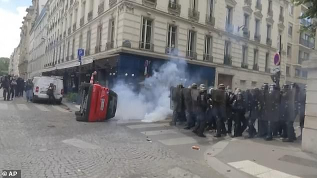 A car was turned over at one point, with demonstrators hiding behind it as they goaded the police