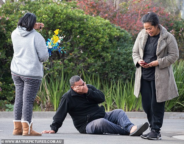 Atunaisa Taufeulungaki collapses to the ground in tears near where his son died as he and his wife Salome prepare to add to the makeshift memorial in honour of their teenage boy