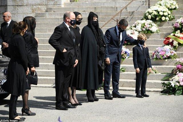 Le couple (centre illustré), arborant des masques noirs et des ensembles assortis, a marché côte à côte alors qu'il menait le cortège funèbre devant la cathédrale de Monaco ce matin.