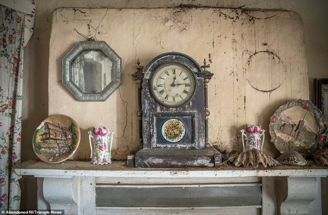 A stopped clock which tells the time 12.15 sits on top of the fireplace in the living room, untouched for decades