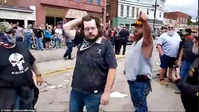 In the shocking video, a man is seen walking through the crowds of armed counterprotesters. He stands not responding to the crowd as they come up close to his face and shout at him