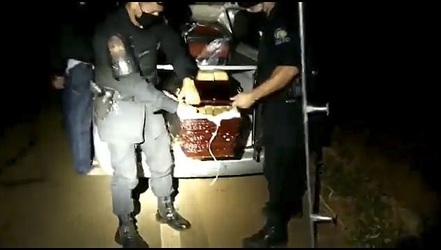 Military police officers in Goiás, Brazil, remove one of two coffins filled with 626 pounds of marijuana following a traffic stop Monday. The driver (left) of the funeral hearse told police he was transporting the remains of two people who had died of the coronavirus