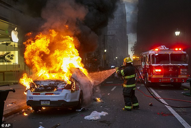 A Philadelphia fire fighter extinguishes a flaming police car in front of the Apple Store on Walnut Street in Philadelphia