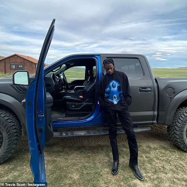 Stylish: the rapper looked stylish with fitted black pants, black boots and a long-sleeved black shirt with a futuristic blue design