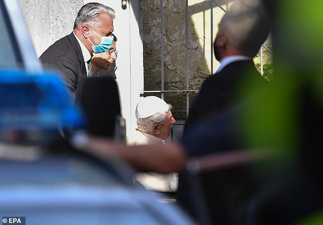 Staff wearing masks take the Pope Emeritus Benedict XVI to the house of his brother Georg Ratzinger in Regensburg