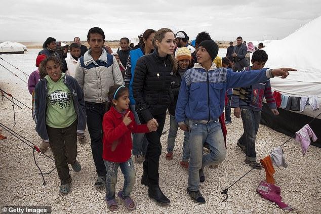 Crash économique: quant à la raison pour laquelle les chiffres ont augmenté si rapidement, Angelina estime que le krach économique de 2008 «a alimenté les difficultés, la colère et le mécontentement» à l'échelle mondiale, ce qui a conduit à une vision déformée des réfugiés;  Angelina photographiée avec des réfugiés à l'extérieur de Mafraq, en Jordanie, en 2012