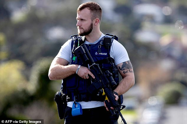 Un officier de police garde la zone après la fusillade dans l'ouest d'Auckland (photo vendredi) avec le tireur toujours en fuite