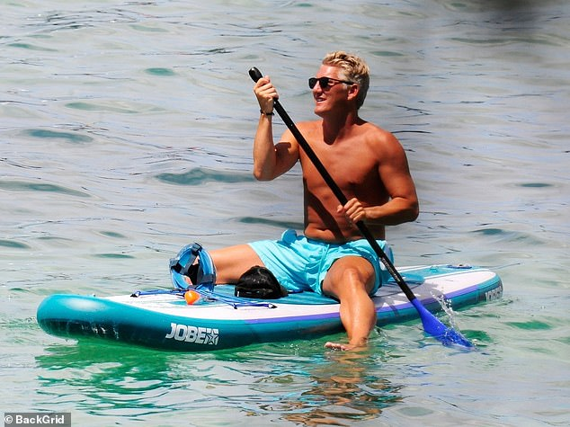 Water sports: Bastian paddleboarded his way to the yacht with ease as he enjoyed the Mallorcan sunshine while the country remains in lockdown