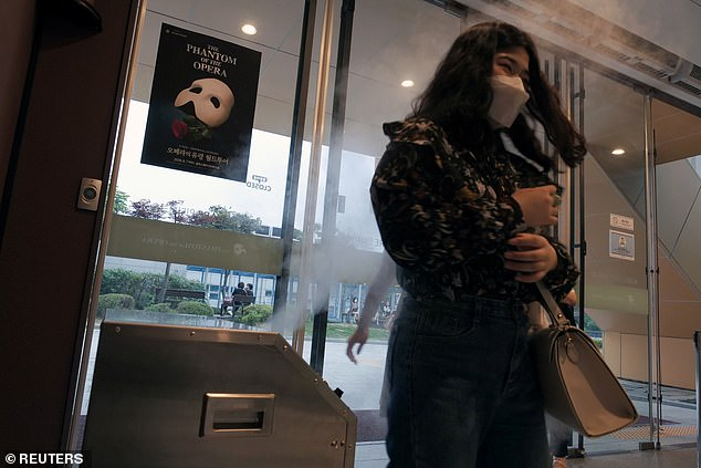 A woman walks past a disinfectant before entering a theater for Phantom of the Opera in Seoul, South Korea, yesterday