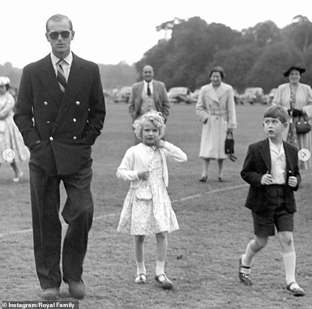 A photo shows a young Prince Philip, elegant in a suit and sunglasses, on a family outing with a young Charles and the Princess Anne, on the photo
