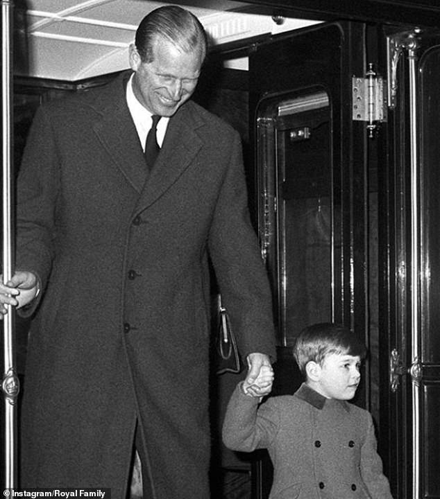 Prince Philip, walking hand in hand with one of his three sons, thought to be Prince Edward