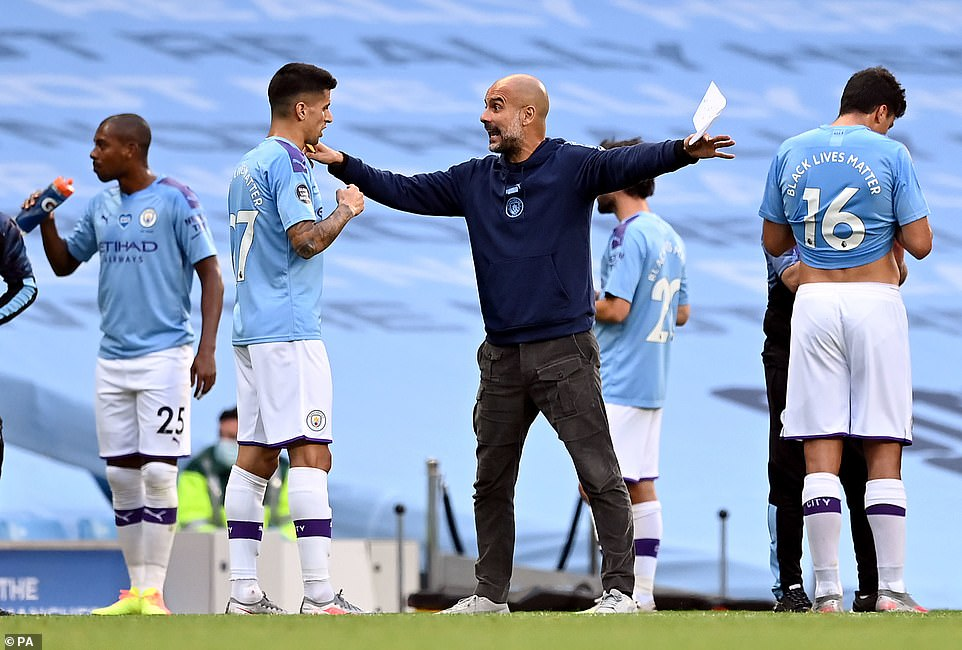 Pep Guardiola dishes instructions to his players during the first-half drinks break as his side looked to take the three points