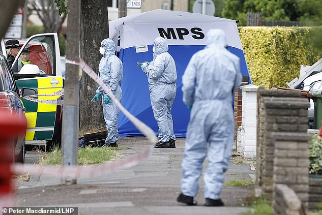 Forensic officers investigate Friday in North Cheam, South-West London, after the shooting