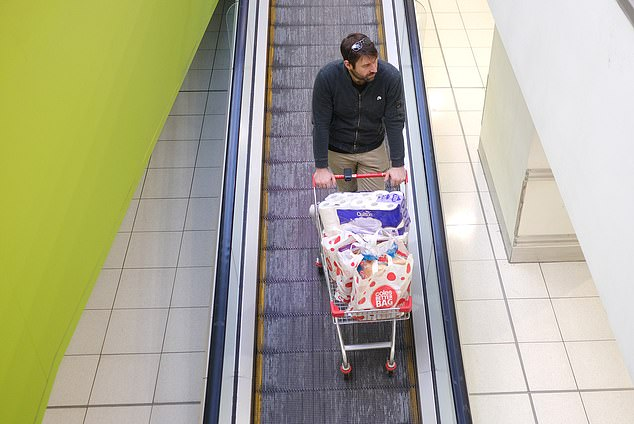A Coles shopper is seen with the grocery bags and toilet paper to Endeavour Hills Shopping Centre on Tuesday
