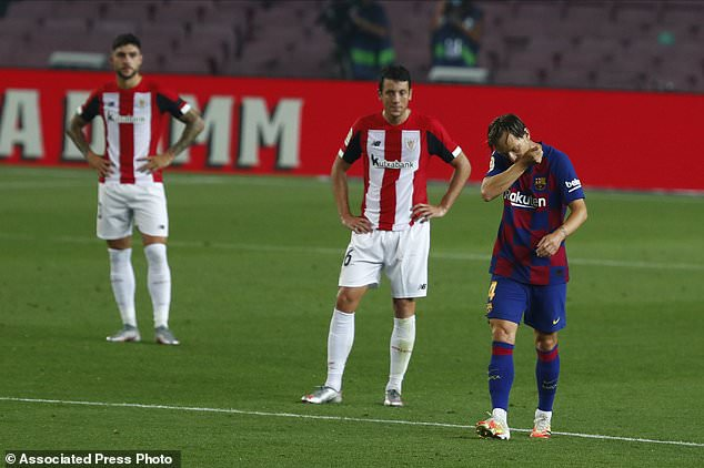 Barcelona's Ivan Rakitic, right, celebrates after scoring the opening goal during the Spanish La Liga soccer match between FC Barcelona and Athletic Bilbao at the Camp Nou stadium in Barcelona, Spain, Tuesday, June 23, 2020. (AP Photo/Joan Monfort)