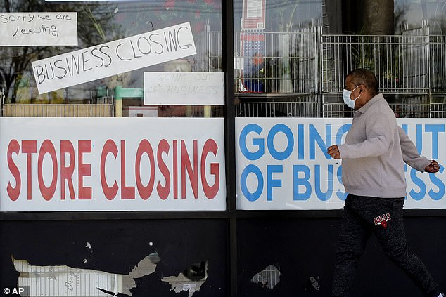 A man looks at the signs of a shop closed due to COVID-19 Niles, Illinois last month. The layoffs in the United States rose in April, revealing the deep hole of economic caused by the pandemic and the closures