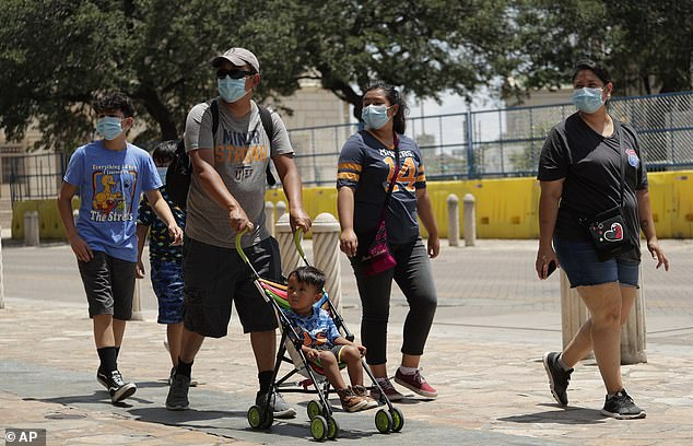 Visitors wearing masks are photographed walking through downtown San Antonio, Texas, as the state is seeing a thousands of new cases of COVID-19 prompting worries from Texas officials