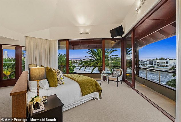 One of the two master bedrooms (pictured) with a balcony overlooking the river and the high-rise skyline of Surfer's Paradise in the distance
