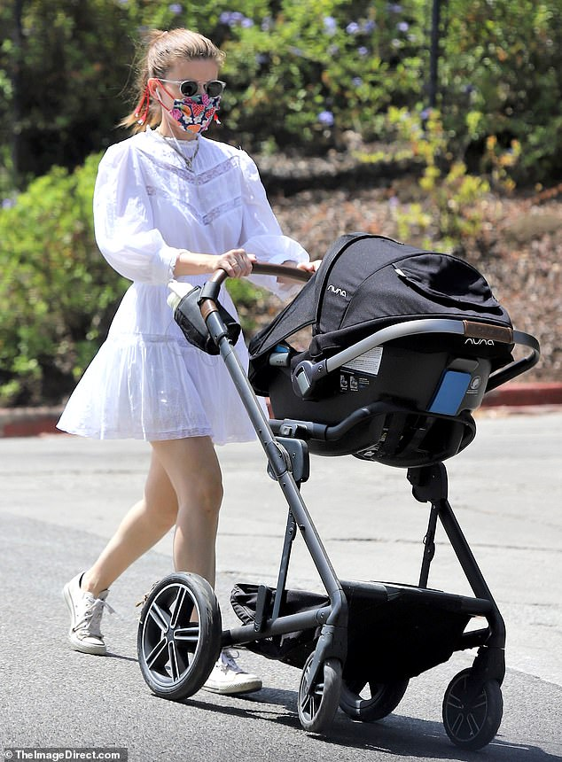 Family time: As the 37-year-old House of Cards star displayed her toned legs in a summery white dress, she pushed her mini-me, whose name has not been disclosed, in a black stroller