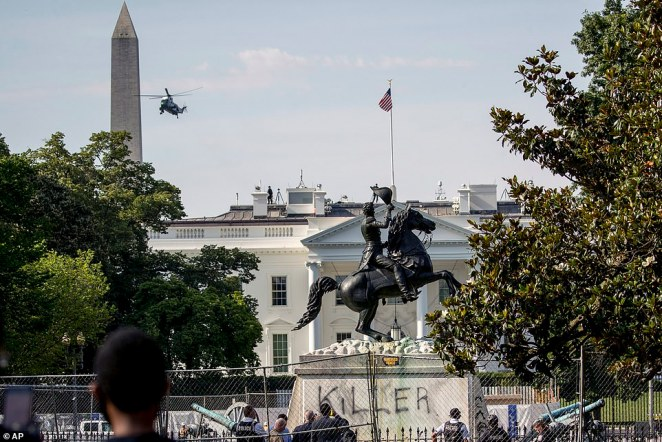 The White House is visible behind the Andrew Jackson statue in Lafayette Park, Washington DC, with the word 'killer' spray painted on its base.President Trump has put US Marshals on standby to help protect monuments across America