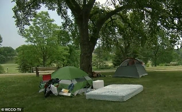Tents and a mattress are set up underneath a tree at Powderhorn Park