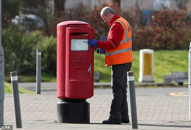 A Royal Mail postman empties a postbox in Glasgow during the coronavirus crisis on April 1