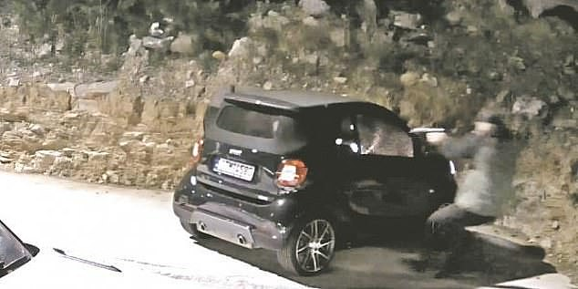 In the footage, Mr Macris sat in his smart car outside of his home when a black-clad man with a baseball cap raced to his car, shooting him four times in the shoulder