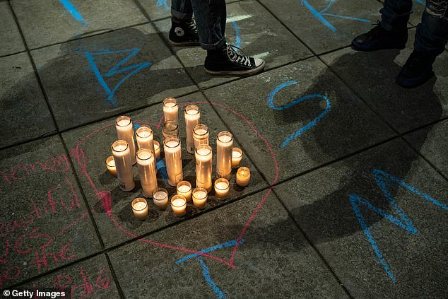 Pictured: Candles for victims of police violence and messages drawn in chalk by protesters are seen at the front entrance to the Seattle Police Department's Wast Precinct after protesters marched there from the area known as the Capitol Hill Organized Protest (CHOP) on June 23, 2020 in Seattle, Washington