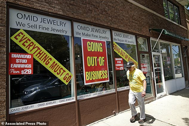 A man walks past a retail store that is going out of business due to the coronavirus pandemic in Winnetka, Illinois on Tuesday