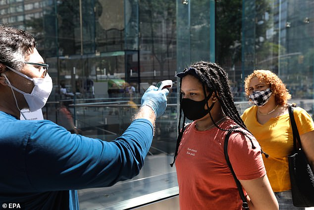 An Apple employee in New York City takes the temperature of a customer before allowing them inside the store