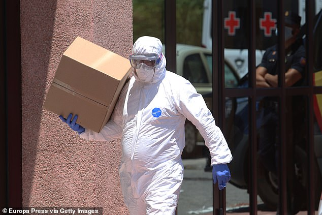 A National Police officer equipped with Personal Protective Equipment (EPI), carries a box at a Red Cross headquarters in Malaga