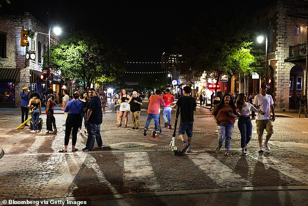 People gather on Sixth Street at night in downtown Austin, Texas on May 23.Texas bars, bowling alleys and other businesses were able to reopen for the start of Memorial Day weekend as part of Governor Greg Abbott's efforts to revive the state's shattered economy