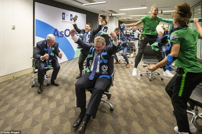 Matildas defenderAlanna Kennedy (right) jumps from her chair and screams as the successful bid is announced
