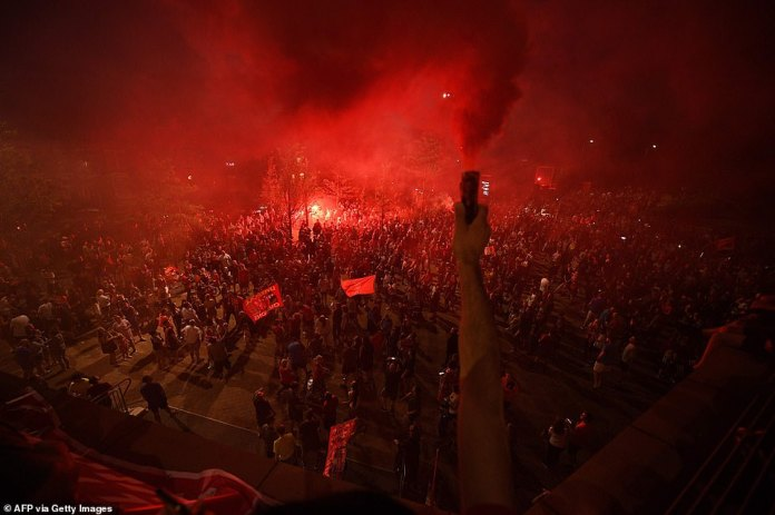 Incredible photos show thousands of Liverpool fans congregating outside Anfield to celebrate the club's title win on Thursday