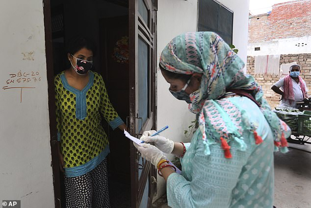 In the photo: A teacher from an Indian government school writes the details of a family during an investigation in a residential area of ​​New Delhi, India, Saturday, June 27, 2020