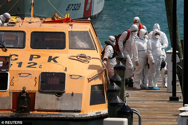 First responders evacuate sick crew members with flu-like symptoms from two cruise ships, the Costa Favolosa and the Costa Magica in Miami on March 26