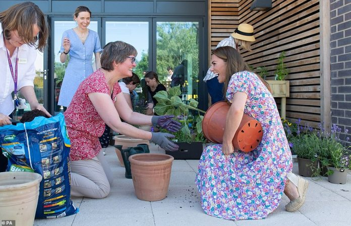 Kate laughs while holding a plant under her arm while helping to potty plants and herbs during a visit to the children's hospice