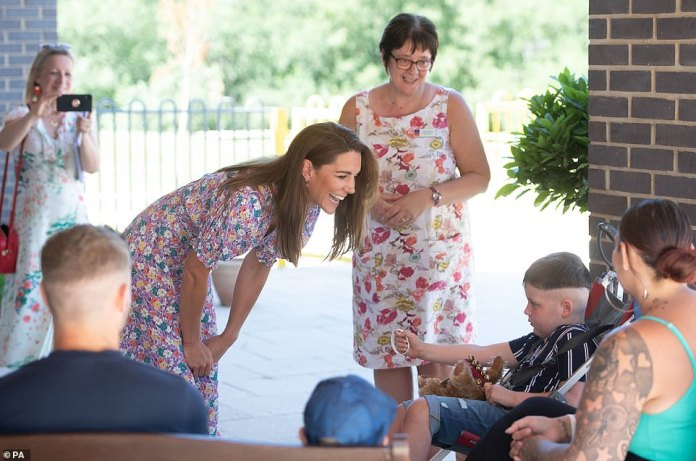 The Duchess of Cambridge meets Sonny Saunders and her family, including mother Kelly (right, back to camera) and father Jordan (left, back to camera)
