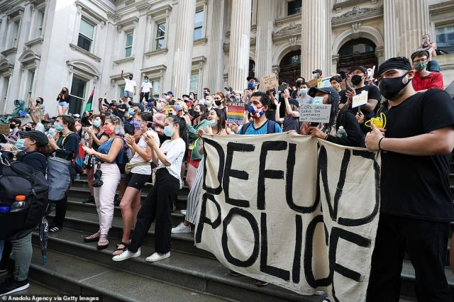 """Protesters sit at the stairs of Tweed Courthouse on Saturday next to the City hall as hundreds of them congregate as part of the """"Defund NYPD"""" and """"Occupy City Hall"""" movement. The protest demands cuts to the NYPD budget"""