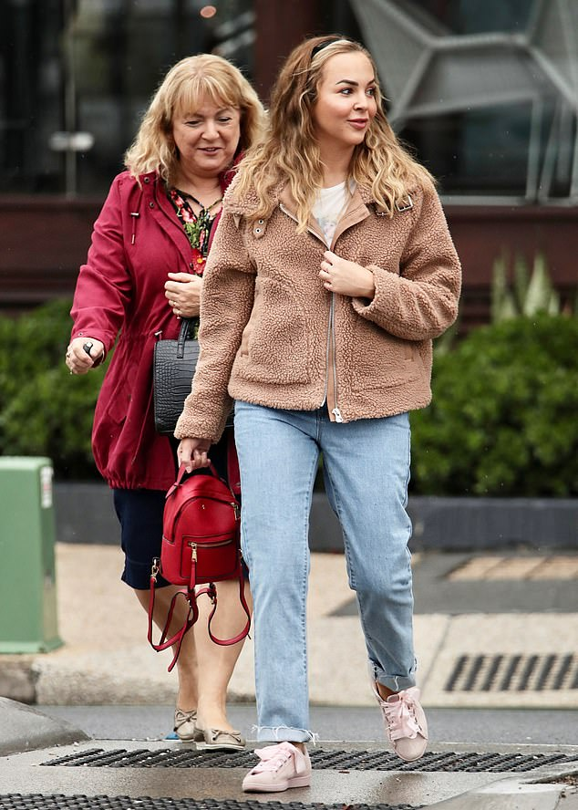 Aussteigen: Die 30-jährige Reality-Starin trug einen beigen Mantel, ein weißes T-Shirt und Jeans und wurde von ihrer Mutter Jane (links) begleitet.