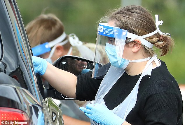 UK: medical worker wearing mask and protective screen, disposable gloves and plastic apron, takes a swap at a coronavirus driving test center in the parking lot of Chessington World of Adventures Resort May, the 1st