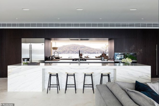 Eat in style! The kitchen is fitted with high-end appliances, a sleek marble island that doubles as a breakfast counter, and a reflective splashback.