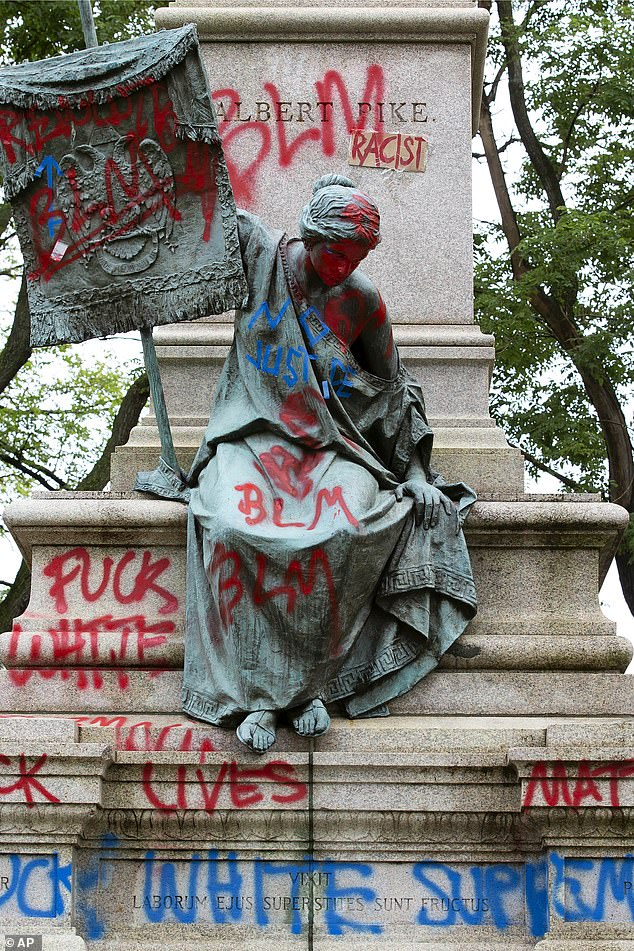 The bronze sculpture representing the Goddess of Masonry on the base of the statue of a Confederate general, Albert Pike, is seen with red paint, after protestors toppled Pike statue's and set on fire