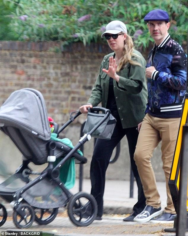 Keeping his new 'do protected:Jimmy Carr covered up the results of his hair transplant as he stepped out for a stroll with his longtime girlfriend Karoline Copping in London on Sunday