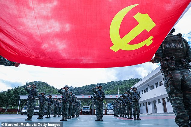 Pictured: Chinese Communist Party members swear their allegiance to the party flag in Yunnan Province on Saturday. China is widely believed to be behind the escalating hack attacks on Australia's cyber infrastructure, but Beijing denies the claim